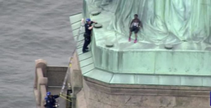Woman protesting migrant separation climbs base of Statue of Liberty, booked
